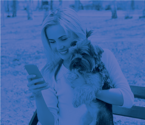 Millenial woman holding her dog and looking at her phone.